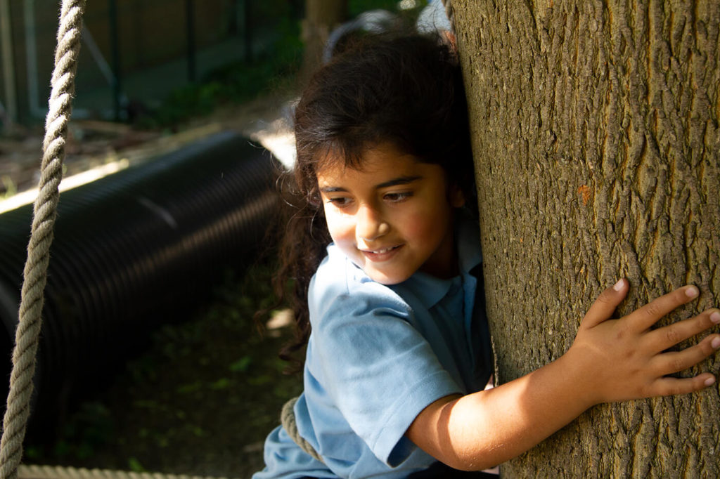 young girl playing around tree in playground