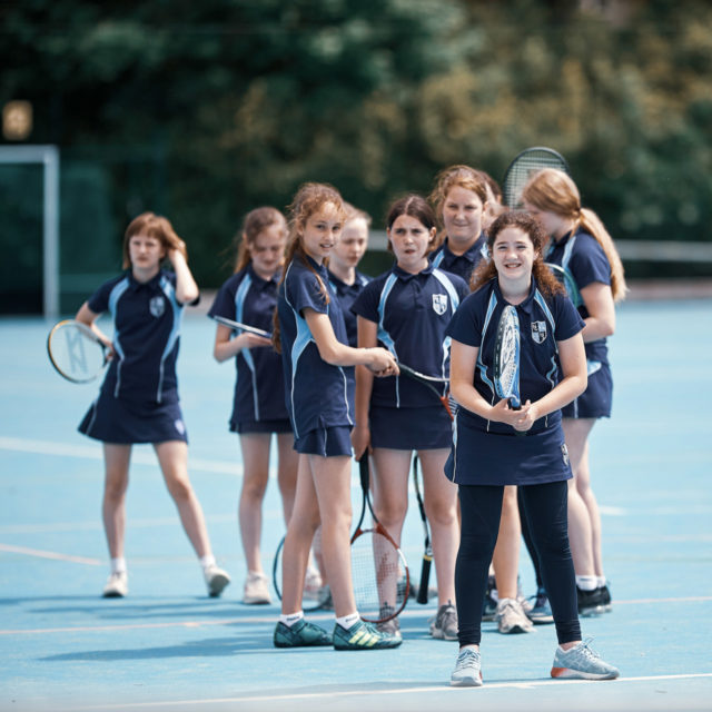 nottingham girls' high school pupils taking turns to hit tennis ball on sports court