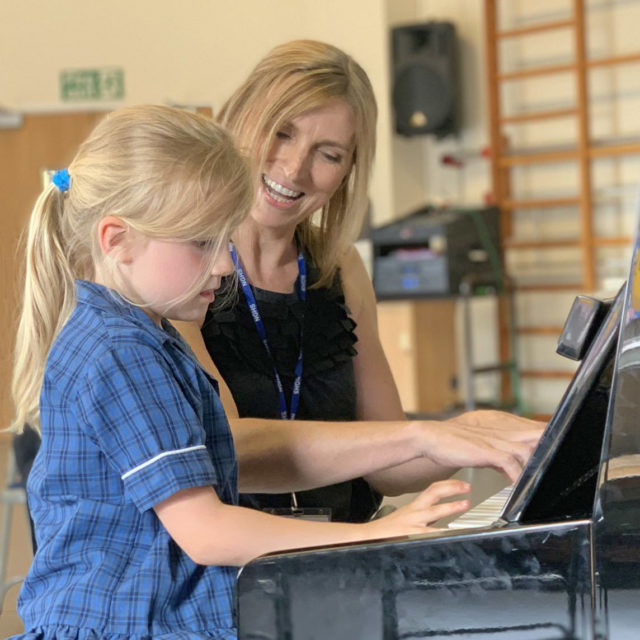 music teacher playing piano with a young student
